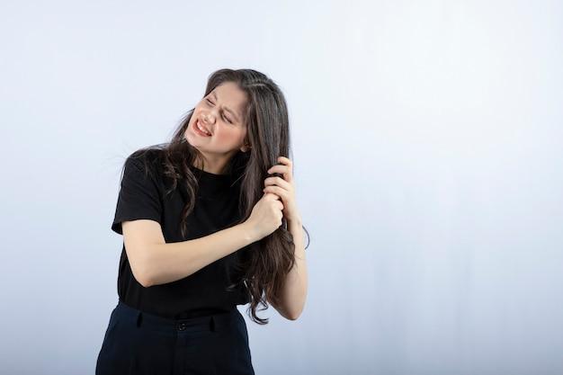 Foto die van donkerbruin meisje haar haar op grijs houdt.