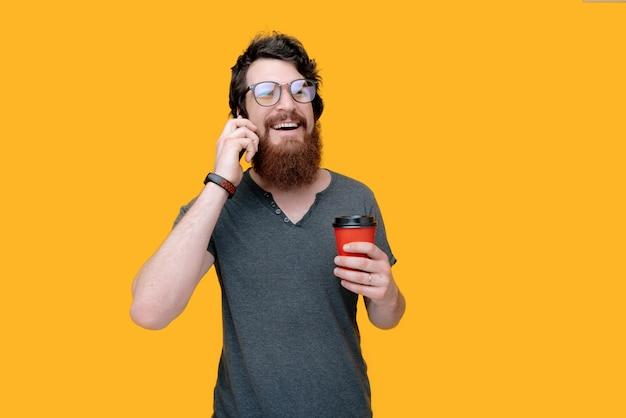 Foto die van gebaarde kerel een rode kop met koffie houdt, en bij telefoon op geïsoleerd geel spreekt