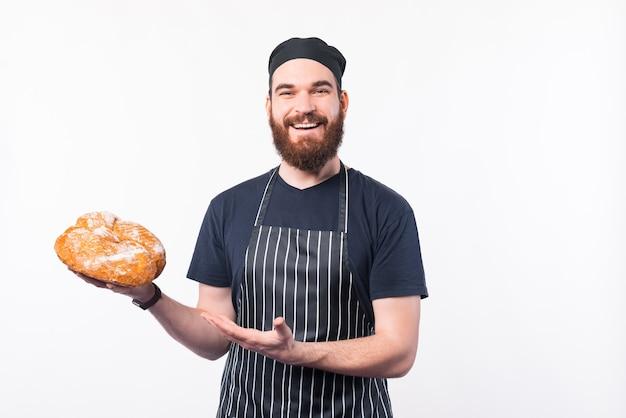 Foto die van gelukkige chef-kokmens vers gebakken brood voorstelt