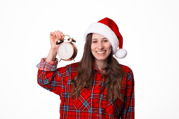 Foto die van jonge vrouw in kerstmissanta hoed en een uitstekende klok op witte achtergrond houdt