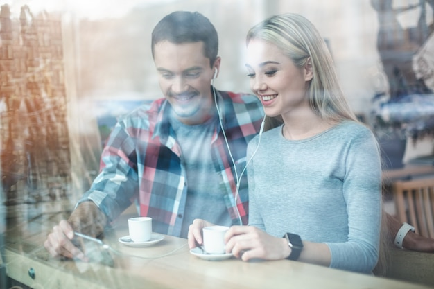 Foto door raam. datum in café. jong koppel in café met stijlvol interieur. studenten met heerlijke koffiedrankjes. ze gebruiken mobiele telefoon