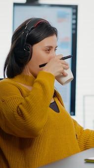 Foto-editor met hoofdtelefoon die afbeelding retoucheert met styluspen