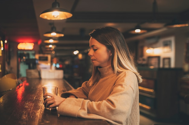 Foto genomen vanaf de zijkant van een jong meisje in een bar alleen met een glas frisdrank
