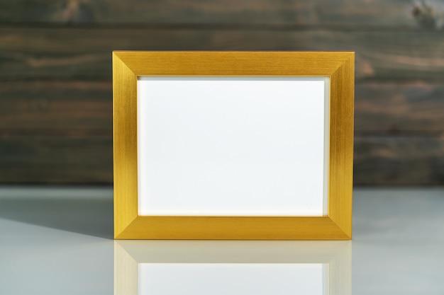 Foto gouden frame mock up en kunstbloemen vaas boeket boven tafel met houten muur achtergrond