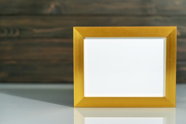 Foto gouden frame mock up en kunstmatige bloemenvaas boeket boven tafel met houten muur achtergrond
