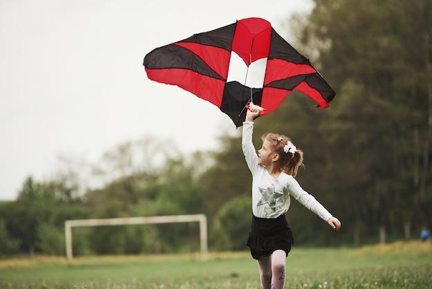 Foto in beweging. gelukkig meisje in vrijetijdskleding met vlieger in het veld. prachtige natuur