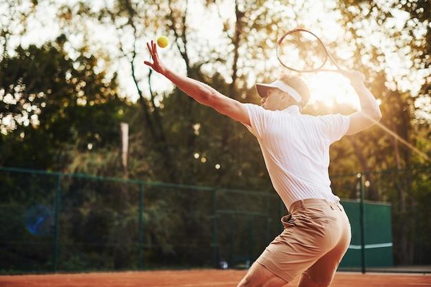 Foto in beweging. jonge tennisser in sportieve kleding is buiten op het veld.