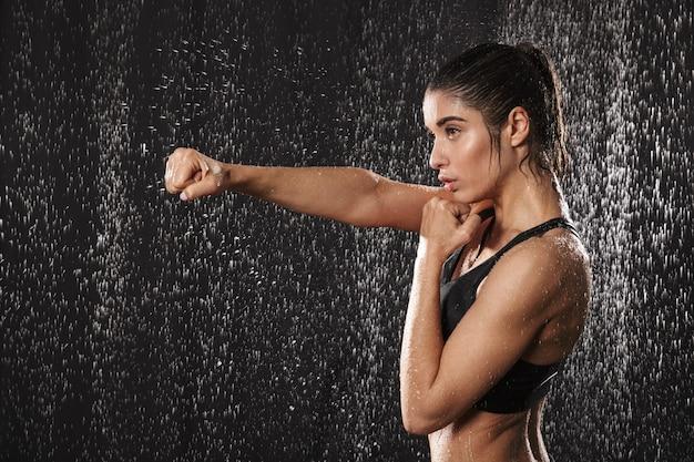 Foto in profiel van gerichte atletische vrouw, gekleed in zwarte sportieve beha punchning met gebalde vuist, geïsoleerd op regendruppels achtergrond