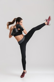 Foto in profiel van gerichte brunette vrouw doet kickboksen oefeningen in bokshandschoenen, over witte muur