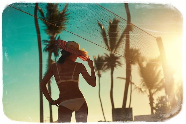 Foto in retro stijl van sexy model meisje in witte bikini met volleybal net op strand en palmen achter blauwe zomer hemel