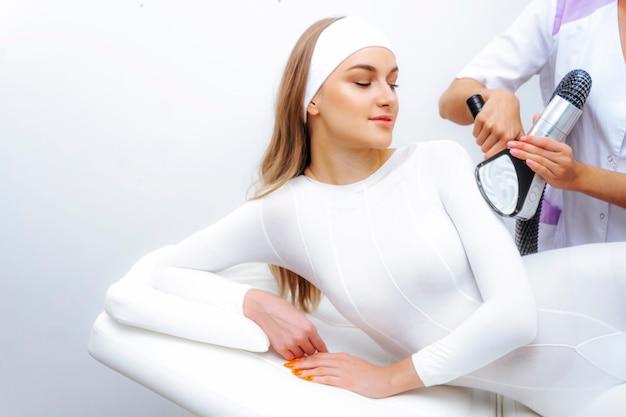 Foto lipomassage lpg. lpg-procedure masseert de patiënt in een wit pak.