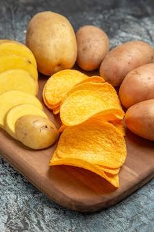 Foto met hoge resolutie van knapperige chips en ongekookte aardappelen op houten snijplank op grijze tafel