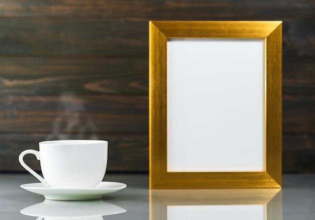 Foto mock-up met gouden frame en koffiekopje boven tafel met houten muur achtergrond