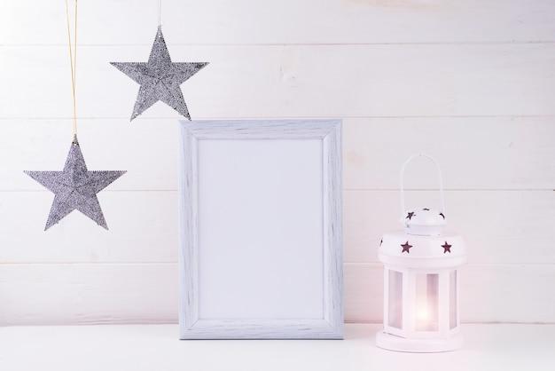 Foto mock up met wit frame, sterren en lantaarn op wit hout