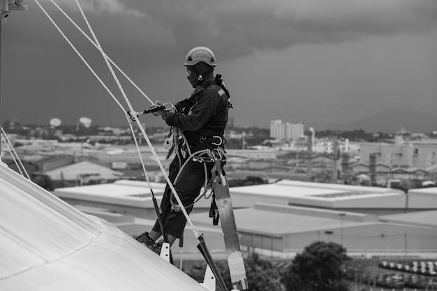 Foto monochrome mannelijke arbeiders controle touw naar beneden boven dak hoogte tank touwtoegang inspectie van dikte schaalplaat opslagtank gasveiligheid werk op hoogte.