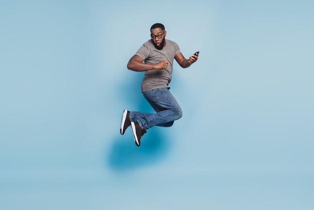 Foto op volledige grootte van afro-amerikaanse man sprong mobiele telefoon geïsoleerde blauwe kleur achtergrond