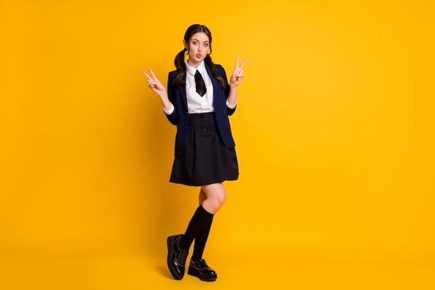 Foto op volledige grootte van droom middelbare school meisje maakt v-teken luchtkus verzenden