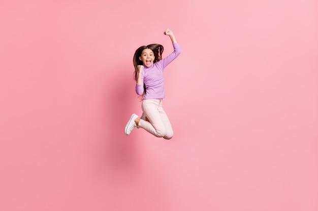 Foto op volledige grootte van een extatisch meisje dat springt, vuisten opheft en een paarse trui draagt, geïsoleerd op een pastelkleurige achtergrond
