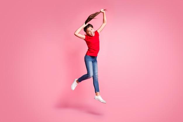 Foto op volledige grootte van een gekke jongen die springt, een paardenstaartkapsel maakt en rode kleding in vrijetijdsstijl draagt, geïsoleerd op een pastelkleurige achtergrond
