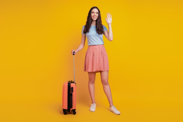 Foto op volledige grootte van een jonge, aantrekkelijke vrouw met een gelukkig positieve glimlachtaskoffer die hallo zwaait, geïsoleerd over een gele kleurachtergrond