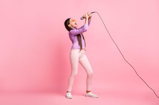 Foto op volledige grootte van een klein meisje dat een lied zingt op de microfoon, een paarse truibroek draagt, geïsoleerd op een pastelkleurige achtergrond