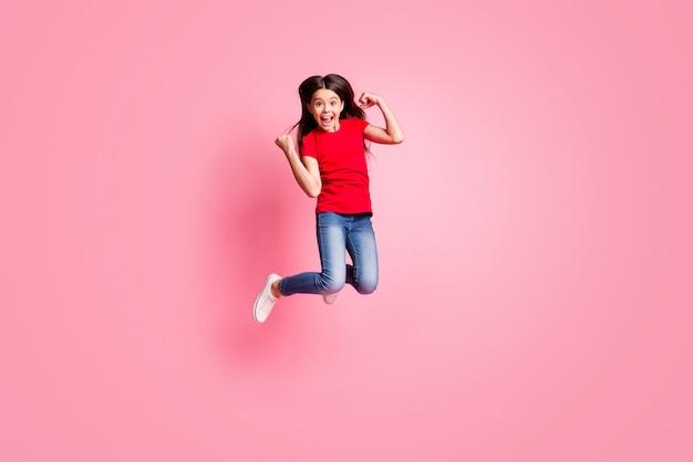Foto op volledige grootte van een opgetogen meisje dat springt, vuisten opsteekt en een casual stijloutfit draagt die over een roze kleurachtergrond wordt geïsoleerd