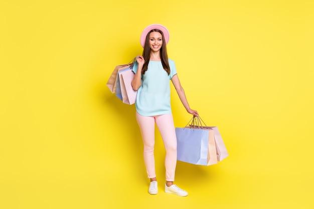 Foto op volledige grootte van een positief reizigersmeisje geniet van rust, ontspan, houd veel tassen, koop ongelooflijke seizoenskoopjes, draag roze blauwe broeken geïsoleerd over heldere glanskleurachtergrond