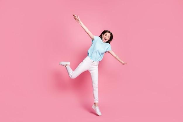 Foto op volledige grootte van een vrolijk meisje dat springt, handen vasthoudt, vliegvogelconcept geïsoleerd over pastelkleurige achtergrond