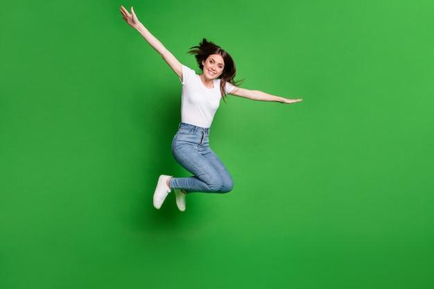 Foto op volledige grootte van een vrolijk meisje sprong hand in hand vliegtuig vliegen spel concept geïsoleerd over groene kleur achtergrond
