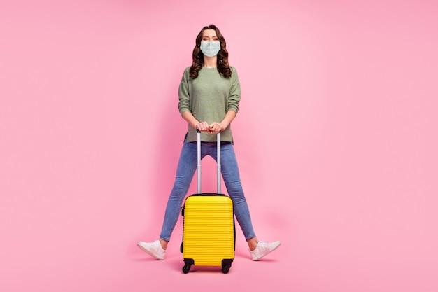 Foto op volledige grootte van een vrolijke, mooie, schattige reiziger, een toeristenmeisje, een koffer, geniet van reizen, covid quarantaine, draag trui, schoenen, medisch masker, geïsoleerd op een pastelkleurige achtergrond