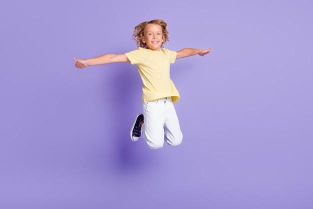 Foto op volledige grootte van kleine jongen springen hand vasthouden vliegen vliegtuig spelconcept draag gele outfit geïsoleerd over violette kleur achtergrond