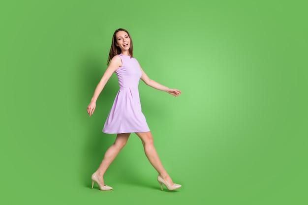 Foto op volledige grootte van schattige slanke jonge meisjesdame die vooruit loopt lege ruimte kijk camera brede glimlach advertentie kleding merk slijtage paarse jurk geïsoleerde pastel groene kleur achtergrond