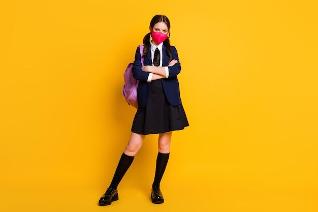 Foto op volledige grootte van slimme middelbare school student meisje kruis handen dragen medisch masker