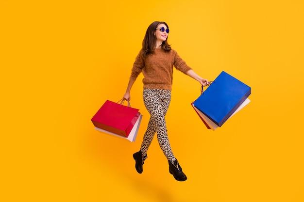 Foto op volledige lengte van een stijlvolle dame die hoog springt en veel boodschappentassen draagt