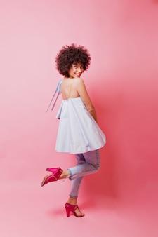 Foto op volledige lengte van stijlvolle charmante vrouw met kort krullend haar, gekleed in blauw shirt, spijkerbroek en roze hakken op roze