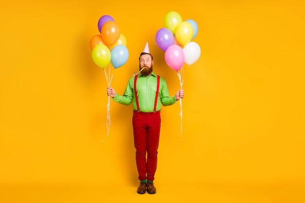 Foto op ware grootte geschokt stupor man bereidt ongelooflijke feestgelegenheid klap lawaaimaker houdt veel luchtballen roze gestippeld draag goed kijken schoeisel geïsoleerde felle kleur