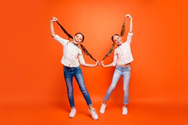 Foto op ware grootte van funky grappig twee kinderen meisje ontspannen vrije tijd herfstvakantie houden paardenstaarten genieten weekenden dragen casual denim kleding geïsoleerde oranje kleur achtergrond
