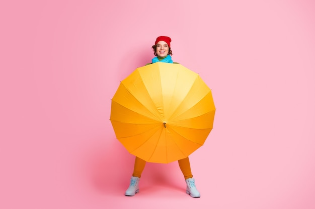 Foto op ware grootte van positief vrolijk meisje opent haar glans parasol verbergen stijlvolle trui dragen wit schoeisel winterkleren geïsoleerd over roze kleur muur