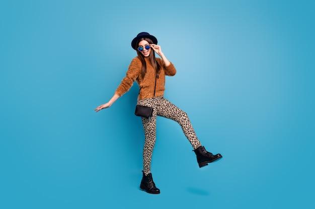 Foto op ware grootte van schattig mooi meisje geniet van herfst plezier weekend vergoeding verheug je grappig funky dromerig draag kleding schoeisel geïsoleerd over blauwe kleur muur
