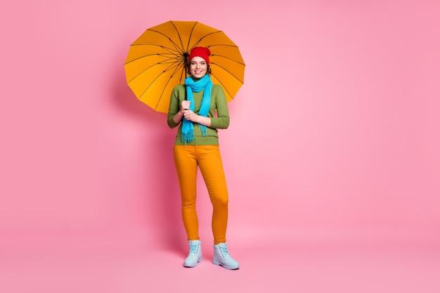 Foto op ware grootte van vrolijk mooi schattig mooi meisje geniet van regenbui reizen vakantie helder houden paraplu dragen casual stijl outfit trui geïsoleerd over roze kleur muur