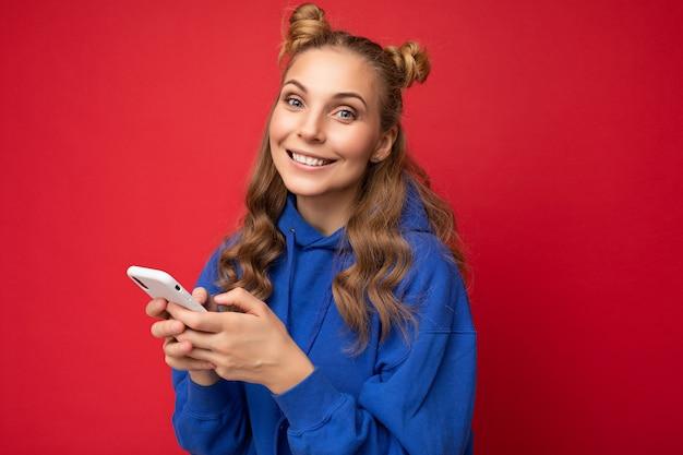 Foto-opname van een aantrekkelijke, goed uitziende jonge vrouw die een casual stijlvolle outfit draagt