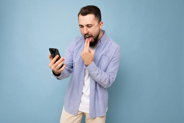 Foto-opname van een boze, knappe, bebaarde, knappe jongeman die een casual stijlvolle outfit draagt