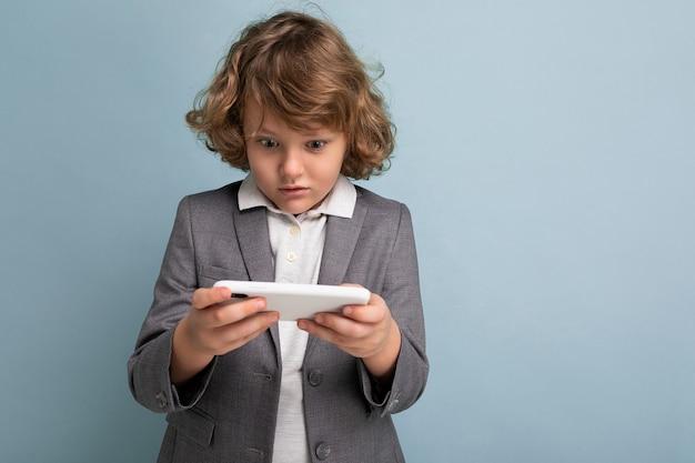 Foto-opname van een knappe emotionele kindjongen met krullend haar in een grijs pak dat een telefoon vasthoudt en gebruikt, geïsoleerd op een blauwe achtergrond, kijkend naar het spelen van smartphonespellen.