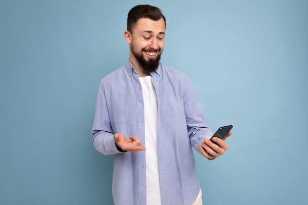 Foto-opname van een knappe, goed uitziende jongeman die een casual stijlvolle outfit draagt