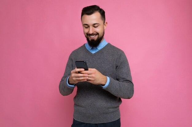 Foto-opname van een lachende, knappe brunet ongeschoren jonge man met baard die een grijze trui draagt