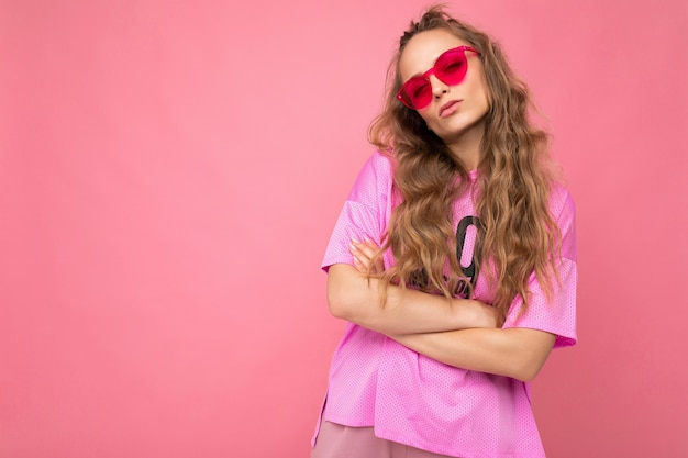 Foto-opname van een mooie jonge donkerblonde vrouw die vrijetijdskleding en een stijlvolle zonnebril draagt, geïsoleerd over een kleurrijke achtergrond en naar de camera kijkt