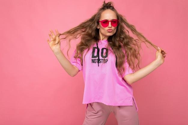 Foto-opname van een mooie jonge donkerblonde vrouw die vrijetijdskleding en een stijlvolle zonnebril draagt