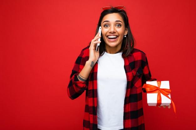 Foto-opname van mooie, vrolijke, jonge brunette vrouw geïsoleerd over rode achtergrond muur background