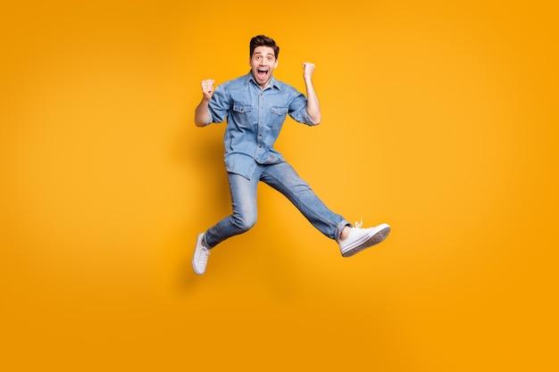 Foto over de volledige lengte van het lichaam van een vrolijke, positieve, dolgelukkige man die enthousiast is over het winnen van wedstrijden die op een geïsoleerde muur met levendige kleuren springen
