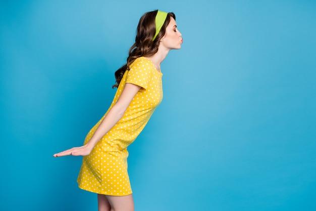 Foto portret profiel van meisje blaast lucht kus geïsoleerd op pastel lichtblauw gekleurde achtergrond